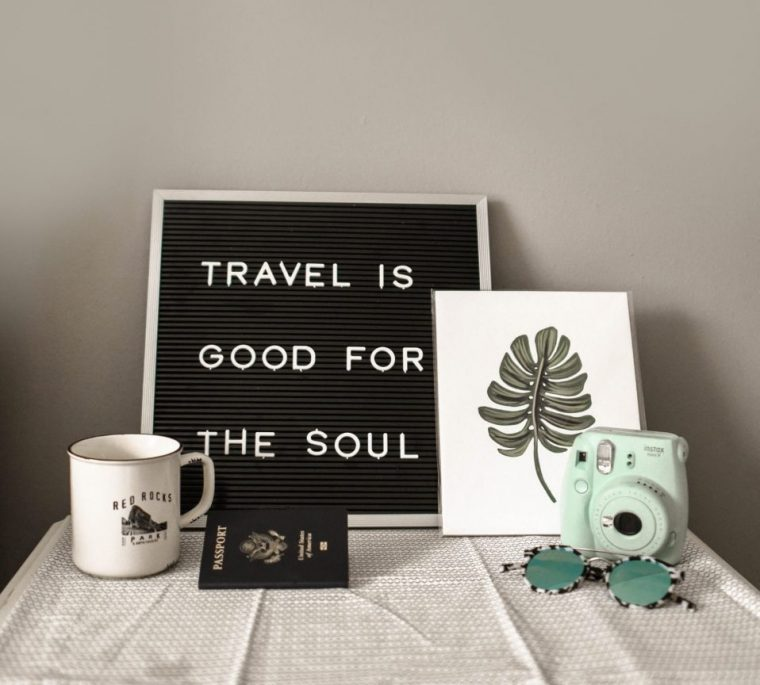 Travel quote on a black board with white letters, green camera and a passport