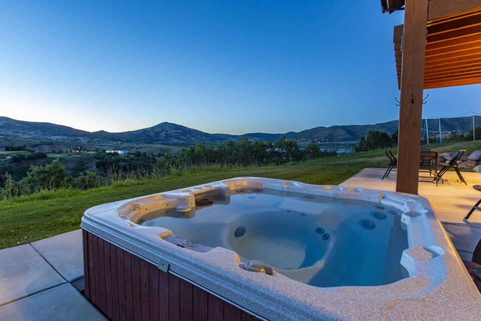 Hot tub overlooking green grass and the sun setting against the mountains.