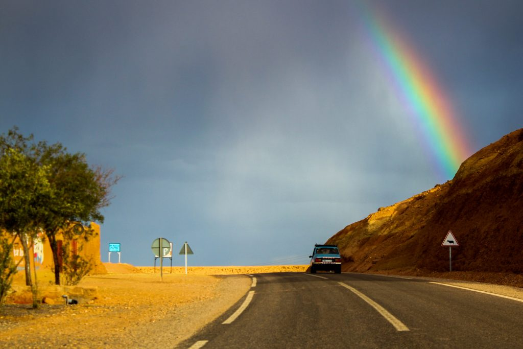 Car driving on an empty road with a rainbow over the road