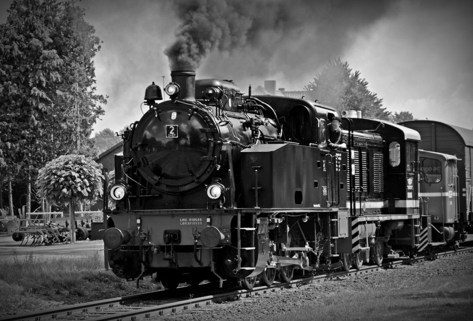 Black and white train with steam coming from the engine.