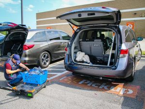 Minivan getting curbside groceries delivered and loaded into their trunk