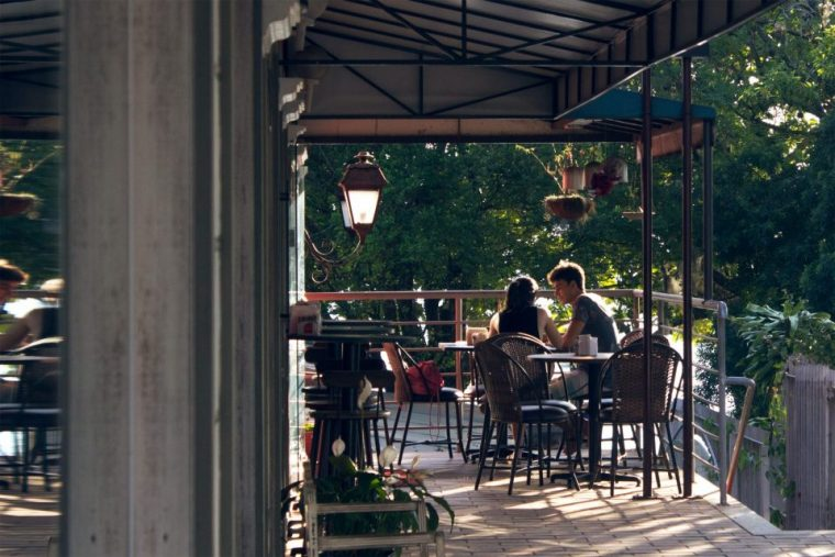 Couple dining in at a Park City restaurant on the wooded balcony
