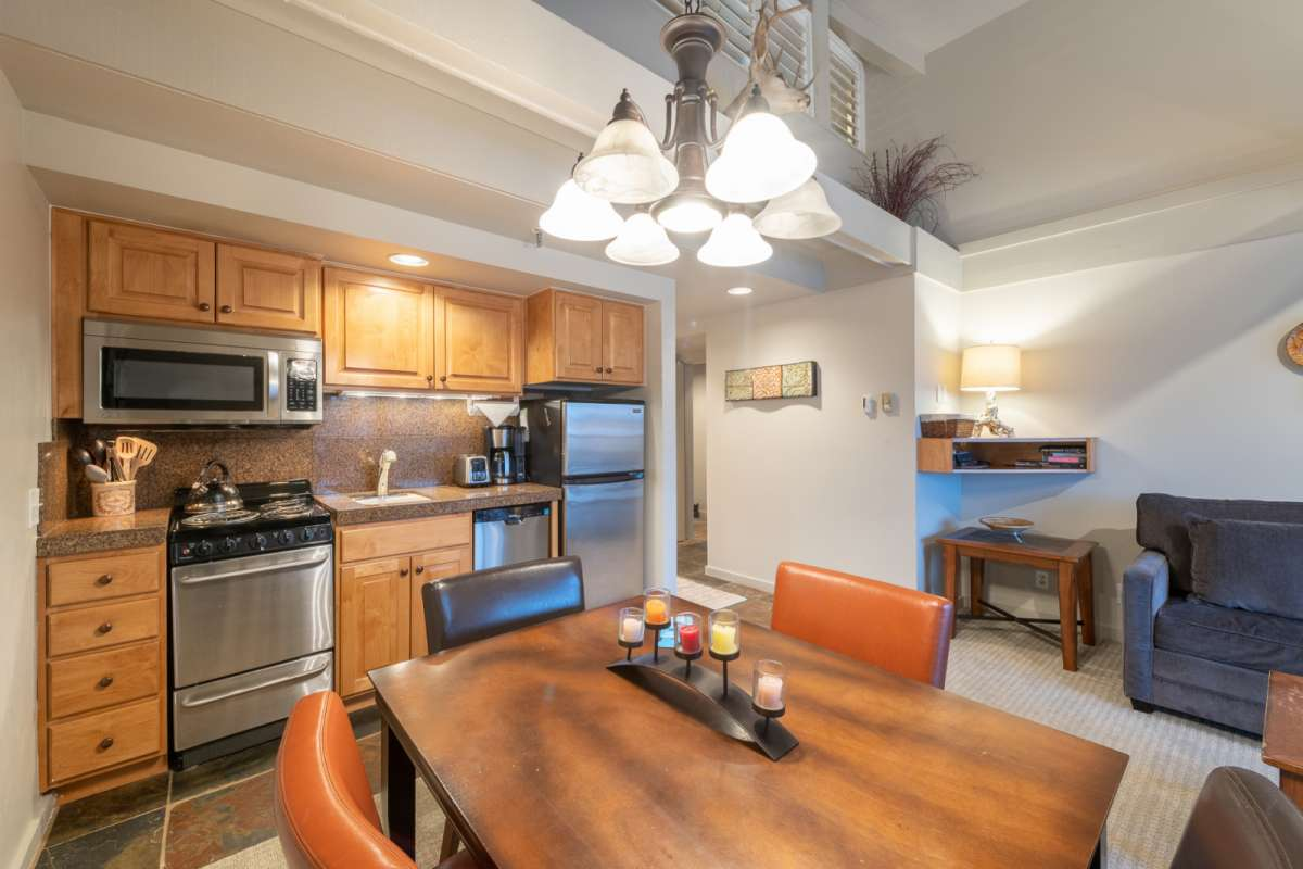 Kitchen with stainless steel appliances, kitchen table in the foreground.